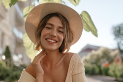 Close-up portrait of lovely white female model with natural make-up expressing good mood. Lovely fair woman in stylish hat holds her chin with her hand.