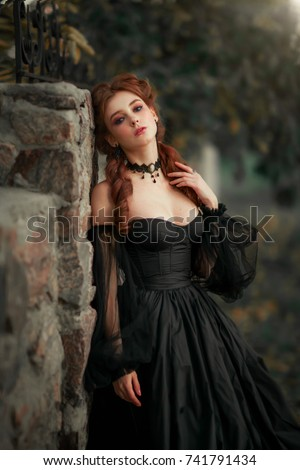 Stock Photo Close up portrait of magnificent Fashion gothic girl near stone wall .Fantasy art work.Amazing red haired model in black dress and hat looking at camera and posing.Fairytale about young princess