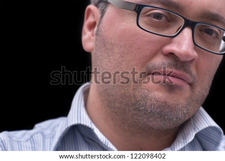 Close up portrait of man with glasses on black background
