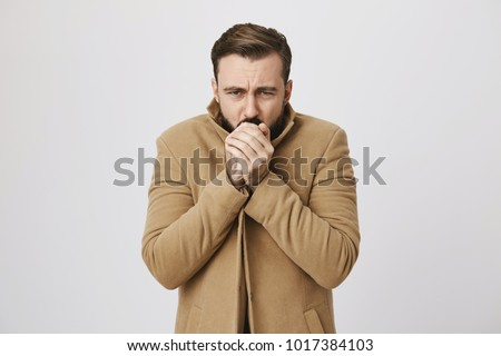 Close up portrait of mature male who feels very cold outside over white background. Man hopes that he will not get cold. Who knew that this day is bad for a date outside. #1017384103