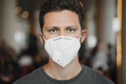 Close-up portrait of Men in respirator mask at the airport. Coronavirus COVID-19 and air pollution concept.
