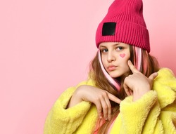 Close up portrait of modern bright confident teen girl on pink background. Child with pink strands of hair dressed in a yellow coat and hat points to a painted heart on his face. Place for text.