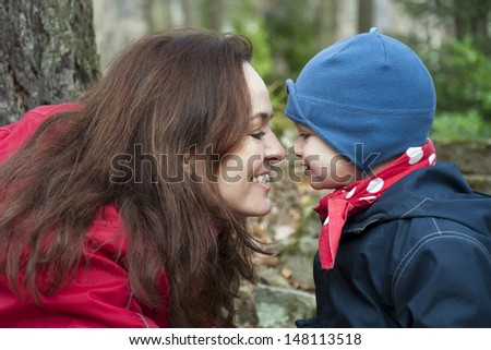 Close up portrait of mother and child, boy or girl, facing each other and smiling in an autumn park.