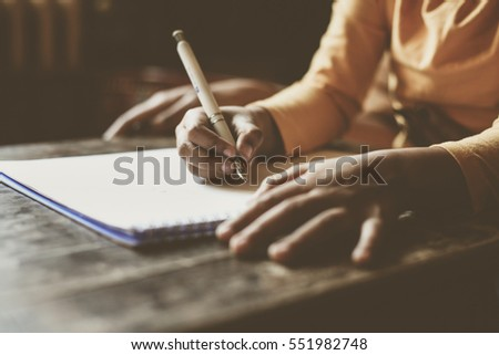 Close up portrait of mother and daughter hands writing.  Space for copy. Focus is on child's hands.