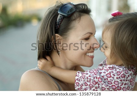 close-up portrait of mother and daughter on the walk in the summer