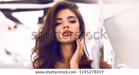 Close-up portrait of natural beauty face with nude makeup. Tender girl with volume brown hair and big lips. Hand near the neck, long eyelashes. White background and high light. #1245278419