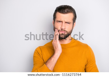 Close up portrait of nervous unhappy troubled handsome bearded man touching his cheek he has toothache isolated on gray background copy-space #1116273764