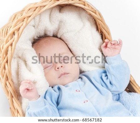 Close up portrait of newborn baby that sleeps in basket with towel on white