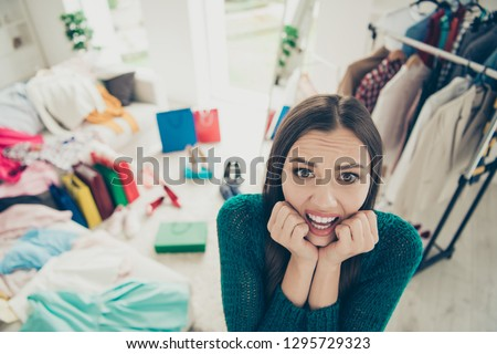 Close-up portrait of nice cute attractive charming pretty scared uncertain worried lady student among different clothes difficult choice problem put on in light white interior dressing room