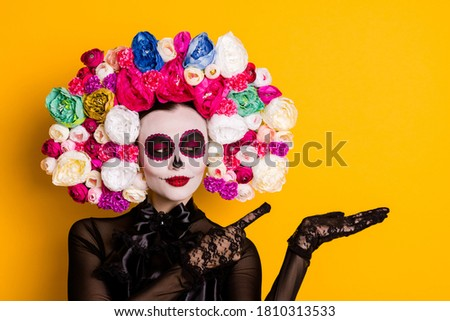 Close-up portrait of nice-looking beautiful glamorous confident lady holding on palm demonstrating copy space advice discount Santa Muerte isolated bright vivid shine vibrant yellow color background