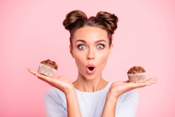 Close-up portrait of nice lovely cute attractive amazed scared afraid girl holding in hands two cakes choosing deciding dilemma opened mouth isolated over pink pastel background
