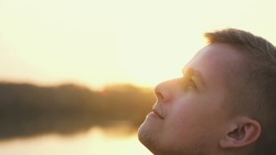 Close up portrait of pensive handsome young man looking up enjoying nature in sun rays at sunset. slow motion.