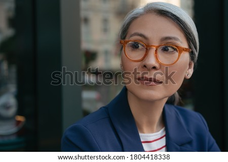 Close up portrait of pensive mature businesswoman looking away, planning start up. Beautiful middle aged woman wearing stylish eyeglasses standing outdoors, focus on face