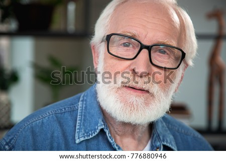 Close up portrait of pensive old bearded man looking at camera. He expresses sincerity, openness while his eye is filled with nostalgia #776880946