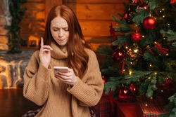Close-up portrait of pensive redhead young woman wearing winter sweater typing online message using mobile phone on background Christmas tree with bright lighting at living room with festive interior.