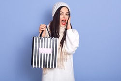 Close up portrait of pleasant adorable beautiful dark haired female holding striped paper bag with present from boyfriend, has astonished facial expression, looks directly at camera with opened mouth.