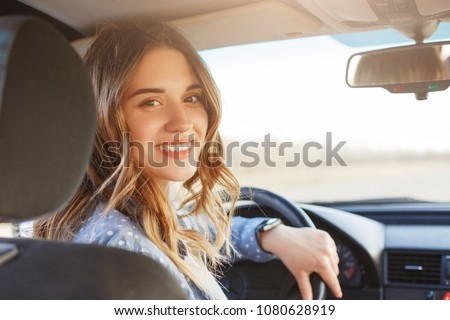 Close up portrait of pleasant looking female with glad positive expression, being satisfied with unforgettable journey by car, sits on driver`s seat, enjoys music. People, driving, transport concept #1080628919