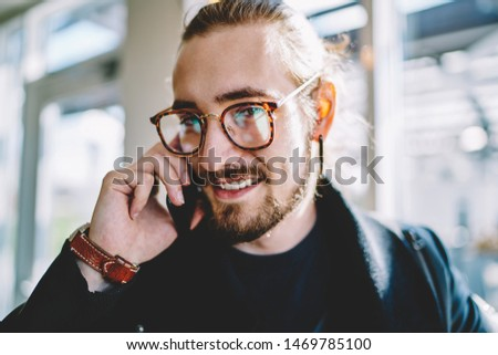 Close up portrait of positive caucasian millennial guy calling to friend via smartphone application connected to 4g,handsome hipster man communicate via cellular phone during leisure on publicity area