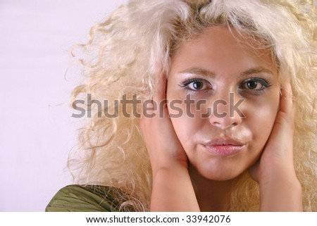 Close-up portrait of pretty blonde woman. Golden blond hair, beautiful black eyes and hot lips. Girl looking at you.