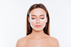 Close up portrait of pretty, charming, attractive girl with naked shoulders using, having, applying patches under close eyes, fight with dark circles, standing over white background, wellbeing concept