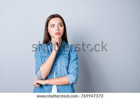 Close up portrait of pretty confident thoughtful girl, holding hand near the face, looking seriously up, standing over grey background with copy space