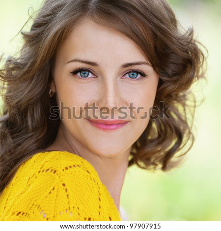 Close-up portrait of pretty young attractive dark-haired curly woman at summer green park.