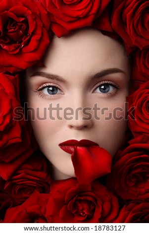 Close-up portrait of pretty young girl in red roses