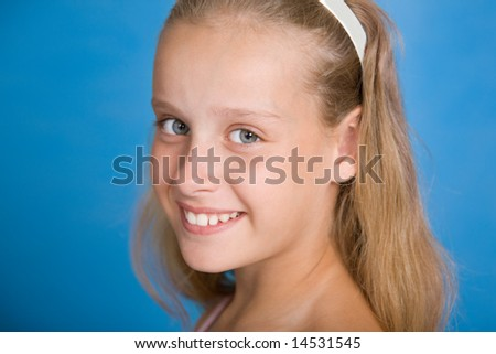 Close-up portrait of pretty young girl isolated on blue