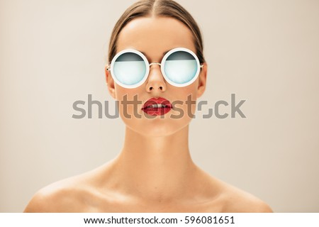 Close up portrait of pretty young woman with glasses against beige background. Female fashion model posing with sunglasses. - Shutterstock ID 596081651