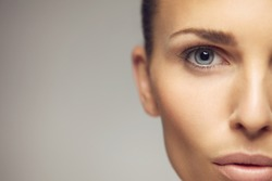 Close-up portrait of pretty young woman with perfect healthy skin and beautiful eyes.  Half face of pretty young female against gray background