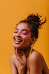 Close-up portrait of refined african lady posing with eyes closed on yellow background. Studio photo of cheerful black girl with pink makeup.