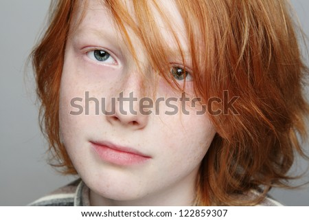 Close-up portrait of sad and thoughtful freckled teen boy looking upwards