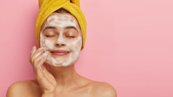 Close up portrait of satisfied beautiful woman massages face, washes with soap, poses bare shouldes, has healthy smooth skin, keeps eyes closed, isolated over pink background free space for your promo