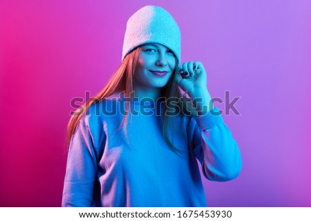 Close up portrait of screaming young woman with knitted cap covering her eyes isolated over pink neon background, lady wearing casual sweater, girl with frisky facial expression. People concept.