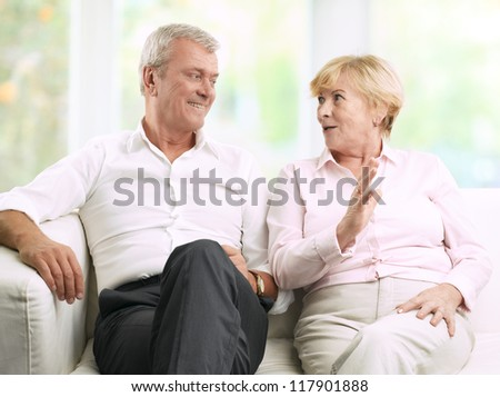 Close-up portrait of senior couple sitting on couch and talking