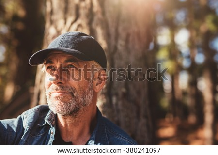 Close up portrait of senior man wearing cap looking away. Mature man with beard sitting in woods on a summer day. #380241097