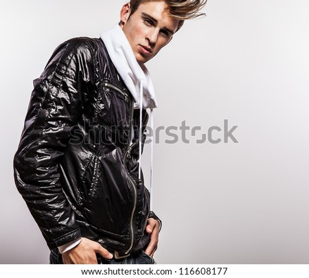 Close-up portrait of sensual young model man on black autumn jacket.