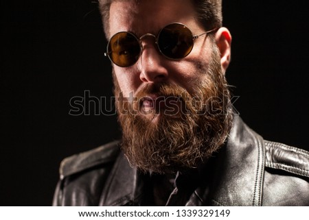 Close up portrait of serious handsome bearded man over black background. Stylish beard. Stylish sunglasses.