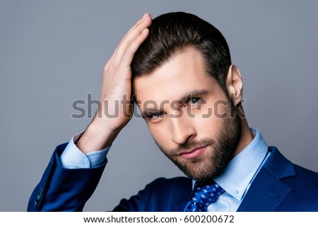 Shutterstock Close up portrait of serious handsome man in blue suit and tie touching his perfect hair