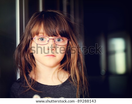 Close-up portrait of serious little child girl wearing glasses, softening filter applied