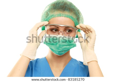 Close-up portrait of serious nurse or doctor in green mask over white background - stock photo