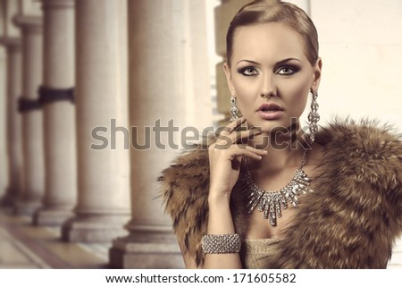 close-up portrait of sexy blonde woman with aristocratic style posing with charming expression and elegant hair-style. Wearing fur shawl and very precious jewellery. Glamour look