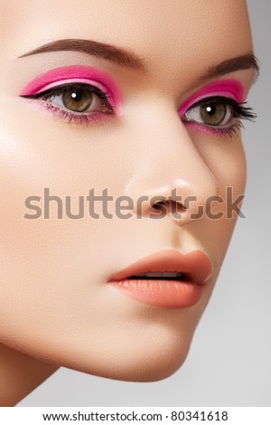 Close-up portrait of sexy caucasian young woman model with glamour eye makeup with arrows, natural lips make-up, purity complexion. Perfect clean shiny skin