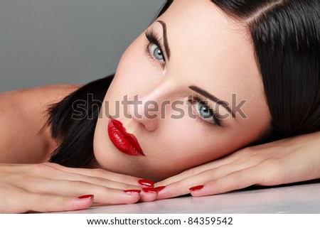 Close-up portrait of sexy caucasian young woman with  make-up and red bright manicure