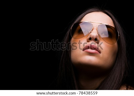 close-up portrait of sexy woman in sunglasses over dark background
