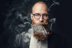 Close up portrait of shaved head aristocratic male in eyeglasses smoking pipe over grey background.