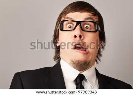 Close-up portrait of shocked businessman, hearing some news. On a gray background