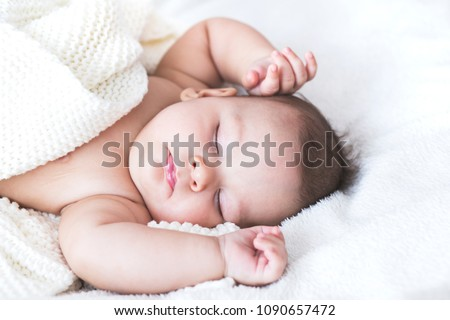Close up portrait of sleeping sweet baby boy in a bright bedroom covered with white blanket. Love, cheerful, mother's care.