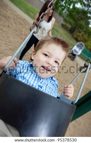 Close-up portrait of small boy swinging while mother standing in background