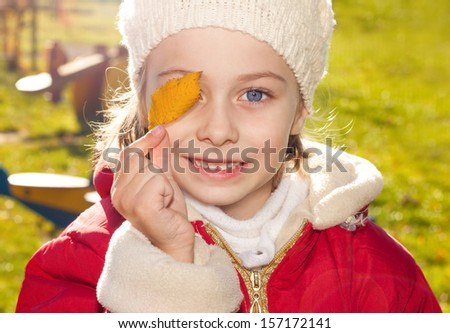 Close up portrait of small five years old happy smiling caucasian girl holding gold leaf outdoor during a sunny autumn day - carefree childhood - stock photo